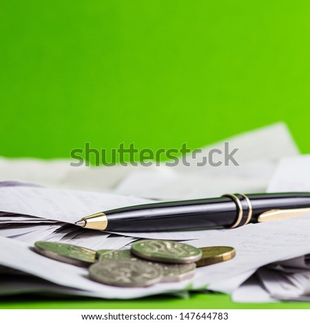 Pen with receipts and coins on green background - stock photo