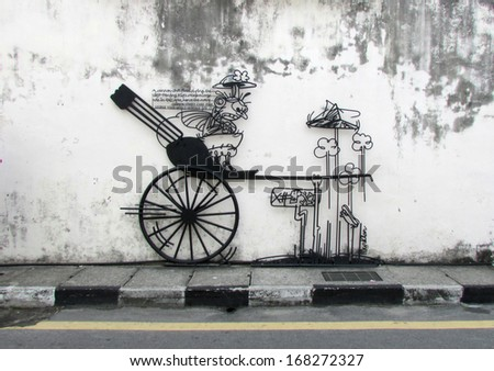"""PENANG, MALAYSIA-Aug 13:General view of steel-rod  Sculpture """"Cannon Hole"""" based on caricature by cartoonist Tang Mun Kian in Penang on August 13, 2013. It is fixed on a wall facing Cannon Street. - stock photo"""