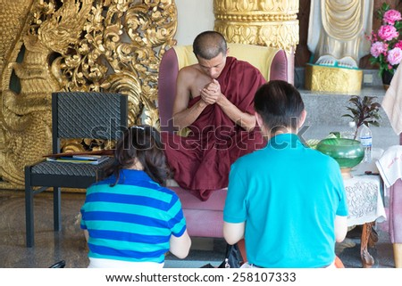 PENANG, MALAYSIA- CIRCA JAN 2015 : Buddhist monk gives blessing to woman and man inside the Dhammikarama, a burmese buddhist temple in Penang Malaysia during Chinese New Year 2014. - stock photo