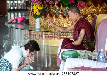 PENANG, MALAYSIA- CIRCA JAN 2015 : Buddhist monk gives blessing to woman inside the Dhammikarama, a burmese buddhist temple in Penang Malaysia during Chinese New Year 2014. - stock photo