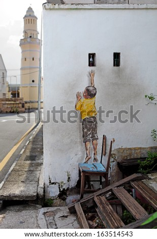 PENANG, MALAYSIA - DEC 13: Street art titled Reaching Up by Ernest Zacharevic in Penang on Dec 13, 2012. It was painted under the Mirrors George Town project for the 2012 George Town Festival. - stock photo