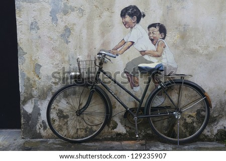 PENANG, MALAYSIA-FEB 14: Street Mural tittle 'Little Children on a Bicycle' painted by Ernest Zacharevic in Penang on Feb.14, 2012.  It was painted in conjunction with the 2012 George Town Festival. - stock photo