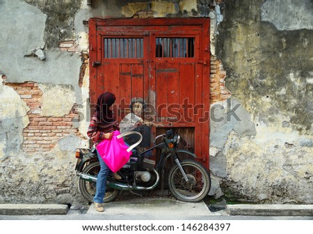 PENANG, MALAYSIA-JULY 6: Muslim girl poses in-front of Street Mural Installation Painting tittle 'Boy on a Bike' painted by Ernest Zacharevic in Penang on July 6, 2013. - stock photo