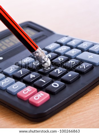 pencil and a calculator on the desk - stock photo