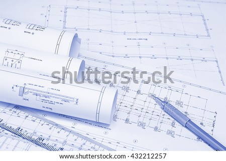 pencil and office tools for writing on the blueprint of construction industry. Place the rolls on a desk over blurred blueprint for construction industry background. construction industry concept. - stock photo