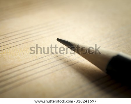 Pencil and old blank sheet music notation, selective focus - stock photo