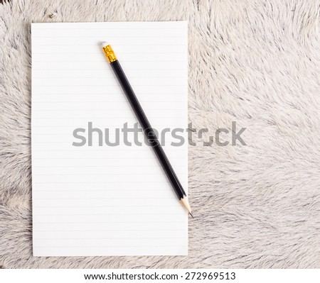 Pencil and  old page ripped off from the notebook on white fur cow skin - stock photo