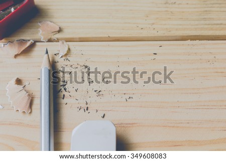 Pencil and red sharpener on wooden table - stock photo
