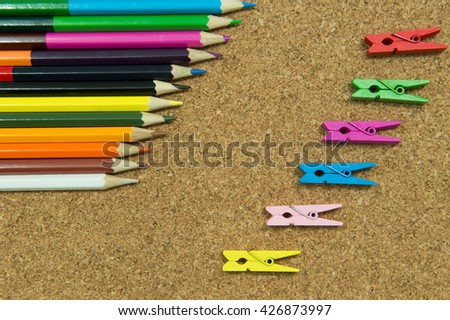 Pencil Crayons and wooden peg on veneer background,selective focus on pencil - stock photo
