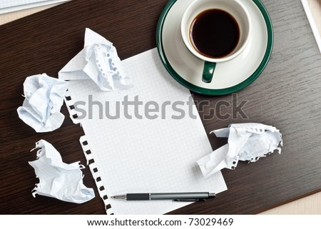 Pencil on a white paper with cup of coffee on dark desk - stock photo