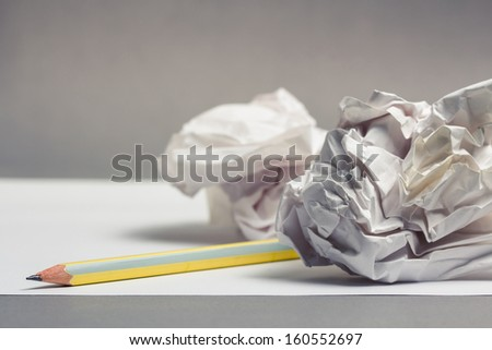 Pencil on clear white paper with crumble paper balls - stock photo