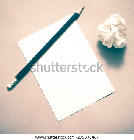 Pencil on clear white paper with crumble paper balls on brown color background vintage style - stock photo