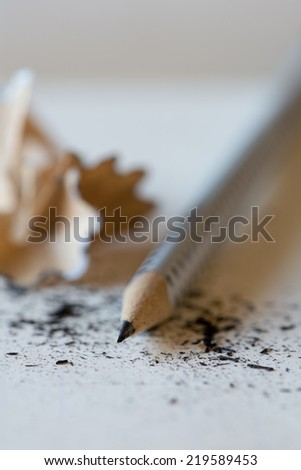 Pencil on table with focus on the tip. Pencil shavings scattered. - stock photo
