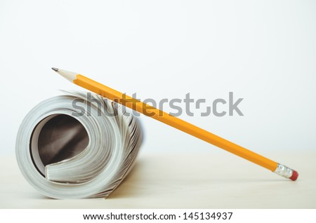 Pencil resting on a rolled up magazine - stock photo