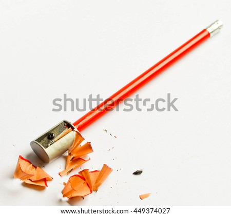 Pencil sharpener and shavings isolated on white background - stock photo