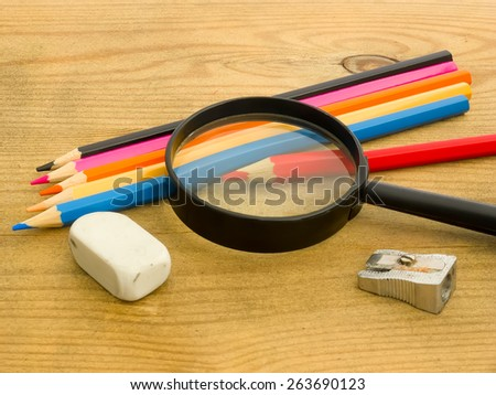 Pencil-sharpener, eraser, and colored pencils under magnifying glass on wooden background - stock photo
