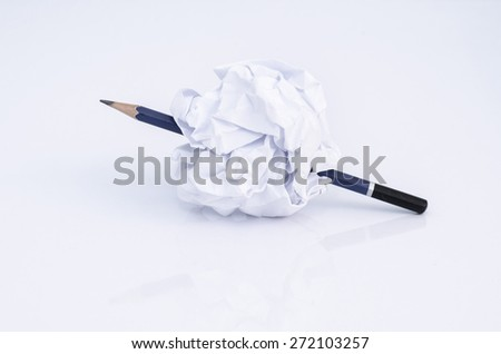 Pencil Stuck Through crumpled paper ball on white background - stock photo