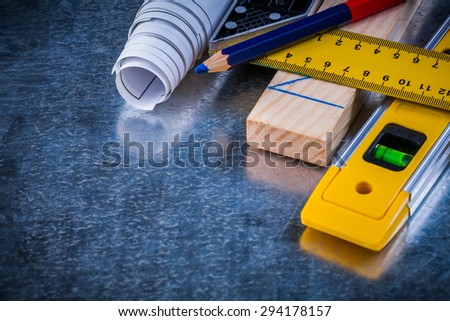 Pencil try square blueprints wooden brick and construction level on metallic scratched surface maintenance concept. - stock photo