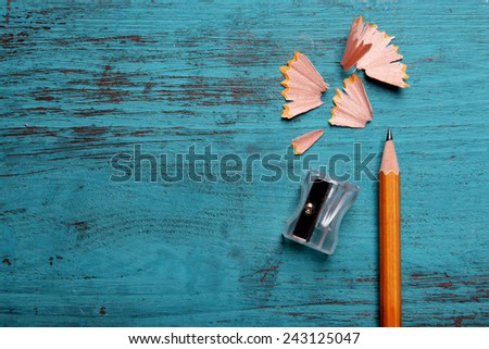 Pencil with sharpening shavings on color wooden background - stock photo