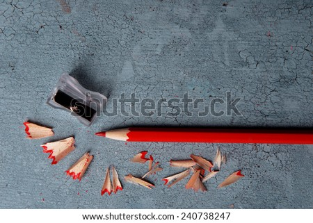 Pencil with sharpening shavings on texture wooden background - stock photo