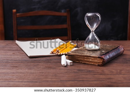 Pencils, book, hourglass and sheets of paper on wooden table - stock photo