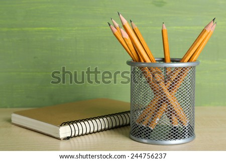 Pencils in metal holder near the notebook on wooden table and green wooden background - stock photo