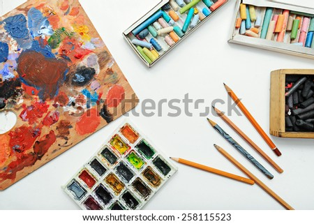 Pencils, paints and palette on paper. Art background - stock photo