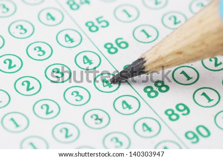 Pencils point at choice No.4 on blank test sheet close up - stock photo