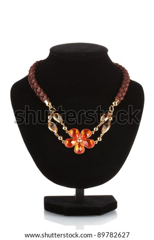 Pendant in form of flower with red gem on mannequin isolated on white - stock photo