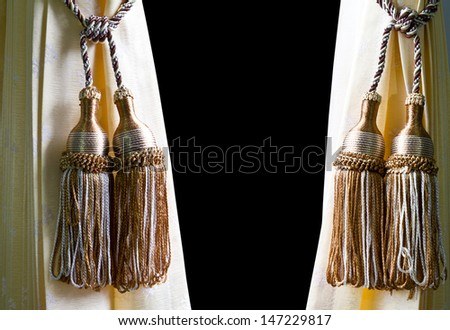 Pendulum made of gold thread on a yellow curtains in the background black. - stock photo