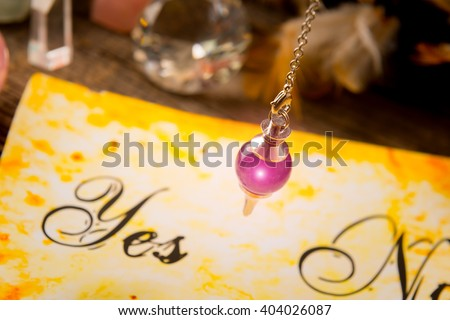 Pendulum, tool for dowsing over yes and no choosing diagram - stock photo