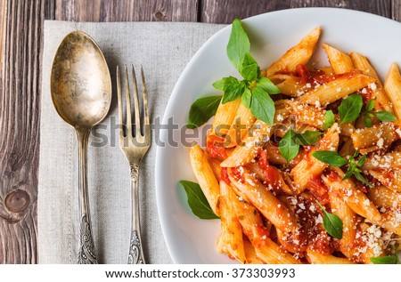 Penne pasta in tomato sauce with basil parmesan cheese on rustic wooden background. Selective focus. - stock photo