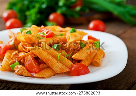 Penne pasta in tomato sauce with chicken and tomatoes  on a wooden table - stock photo