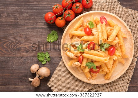 Penne pasta in tomato sauce with chicken on a wooden background. - stock photo