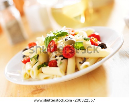 penne pasta salad with olives, tomatoes, and basil. - stock photo