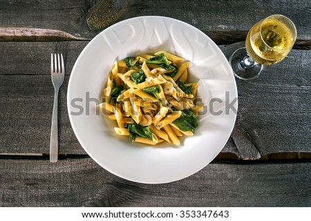 Penne pasta with a creamy sauce with parmesan cheese and basil on a white plate on a wood background isolated. Penne pasta with blue cheese sauce and spinach with vine glas and fork. - stock photo