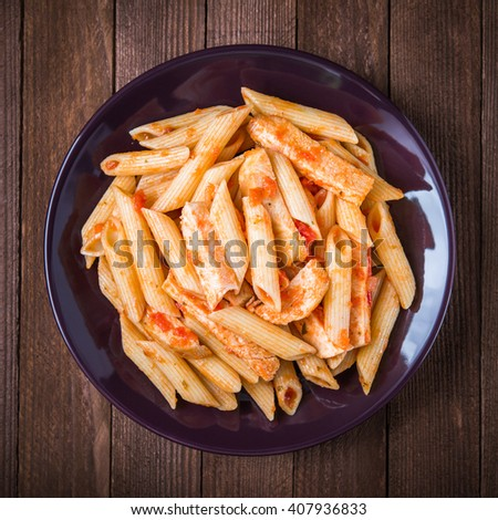 Penne pasta with chicken and tomato sauce on dark wooden background top view. Italian cuisine. - stock photo