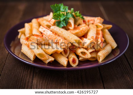 Penne pasta with chicken, tomato sauce and parsley on dark wooden background close up. Italian cuisine. - stock photo