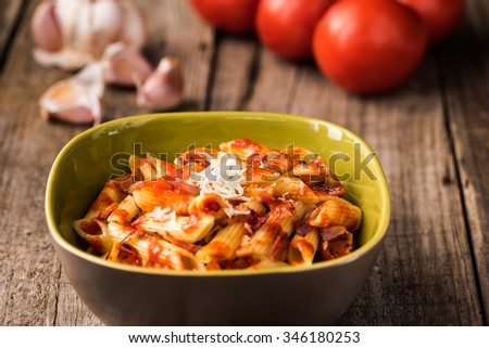 Penne Pasta with Chorizo Creamy Tomato Sauce on Rustic Table Top - stock photo