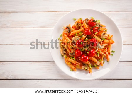 Penne pasta with meat, tomato sauce and vegetables - stock photo
