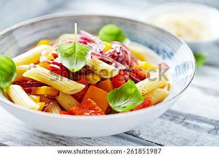 Penne pasta with peppers and basil - stock photo