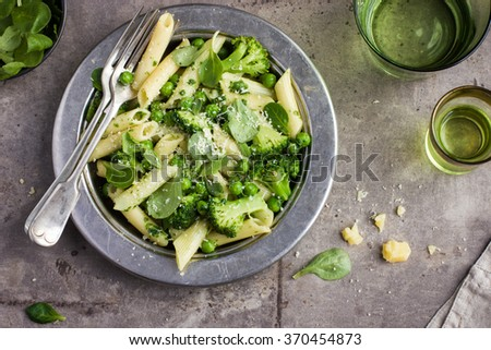 penne  pasta with spinach pesto sauce, green peas and broccoli,  top view - stock photo