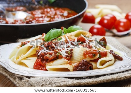 Penne with dried tomatoes. Italian cuisine, delicious, popular dish.  - stock photo
