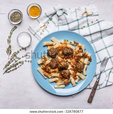 penne with  meatballs Sicilian by on a blue plate with a fork and spices on a checkered napkin on rustic wooden background close up top view - stock photo