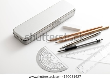 Pens and pencils lying on a table outside of the case. - stock photo