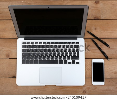 Pens and smart phone near open notebook on wooden background, top view - stock photo