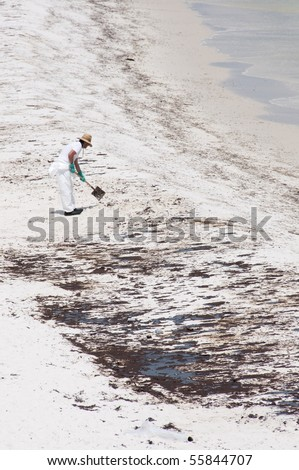 PENSACOLA BEACH - JUNE 23:  A BP oil worker attempts to clean oil covered sand on June 23, 2010 in Pensacola Beach, FL. - stock photo