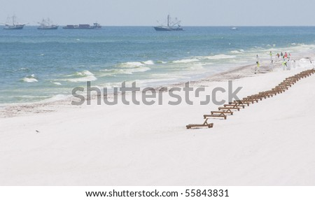 PENSACOLA BEACH - 23 JUNE:  A long row of deserted beach lounge chairs lie on the beach on June 23, 2010 in Pensacola Beach, FL. - stock photo