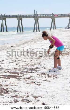 PENSACOLA BEACH - JUNE 23: An unidentifed beach goer looks at oil patches on June 23, 2010 in Pensacola Beach, FL. - stock photo
