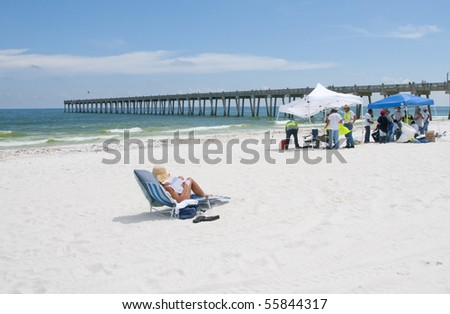 PENSACOLA BEACH - 23 JUNE: An unidentified beach goer rests on the beach on June 23, 2010 in Pensacola Beach, FL. - stock photo